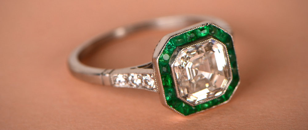 Asscher cut diamond surrounded by a halo of emeralds ring