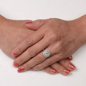 cushion cut halo diamond ring on a finger