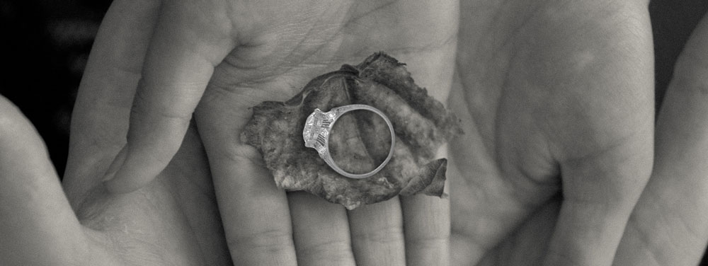 platinum engagement ring on hands and leaf