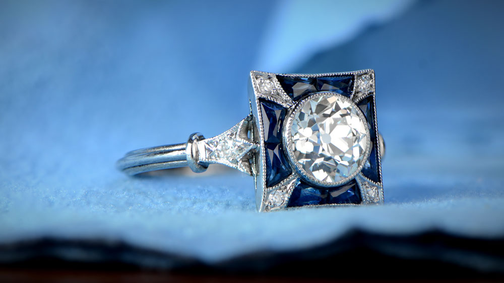 Sapphire and Diamond Engagement Ring on Cloth Surface