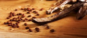Carobs with carob seeds on table