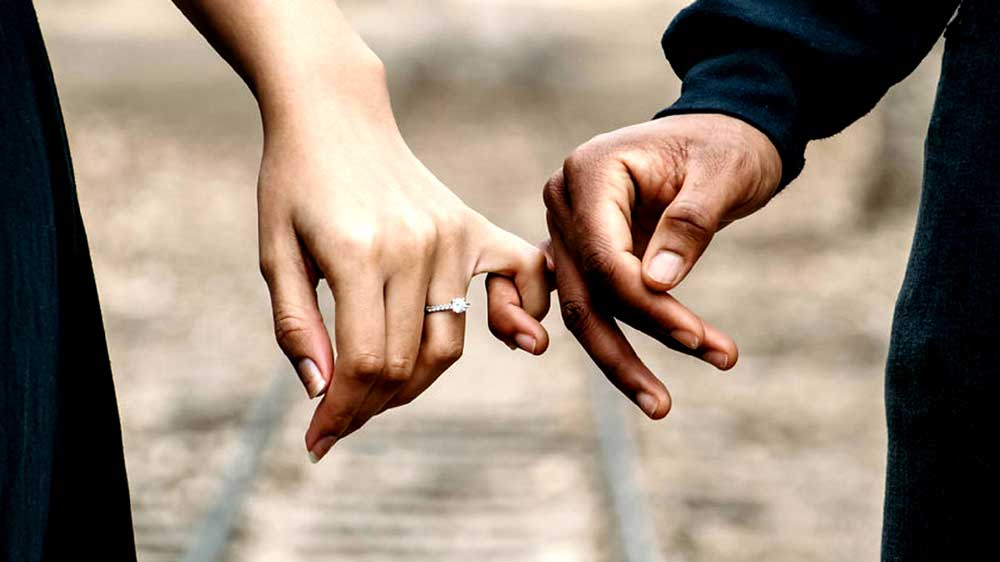Couple Holding Hands and Engagement Ring