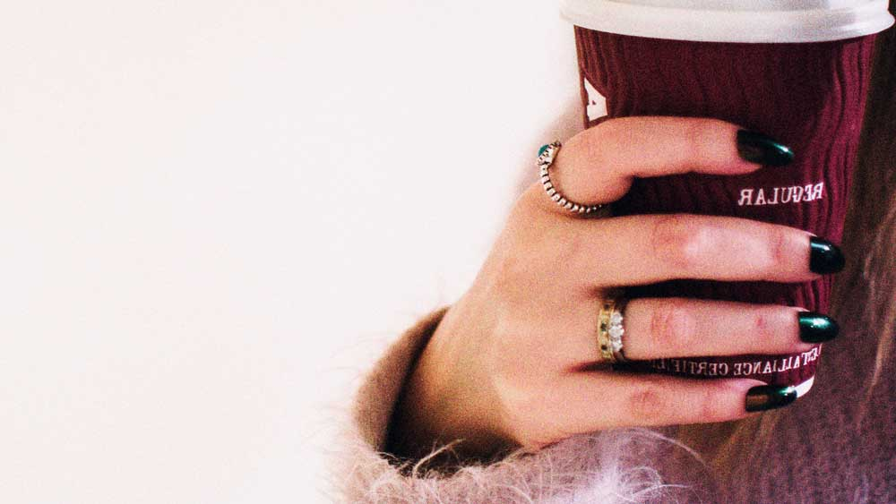 Girl wearing rings on finger with coffee